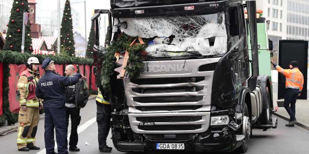 Un policier et un pompier le 20 décembre près du camion utilisé dans l'attaque sur un marché de Noël de Berlin la veille.