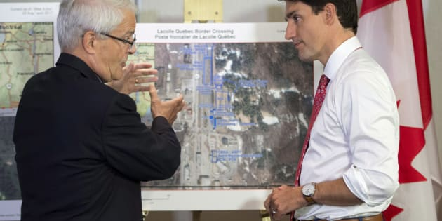Prime Minister Justin Trudeau is briefed on the refugee installations at the Lacolle border crossing by Transportation Minister Marc Garneau prior to a meeting with the Intergovernmental Task Force on Irregular Migration on Aug. 23, 2017 in Montreal.