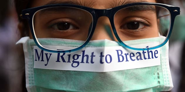 TOPSHOT - An Indian youth wearing a pollution mask participates in a march to raise awareness of air pollution levels in New Delhi on November 15, 2017.