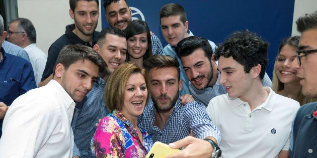 La candidata a las primarias del Partido Popular María Dolores de Cospedal (c) se hace un 'selfie' con miembros de Nuevas Generaciones durante el encuentro con militantes en el Real Casino de Murcia.