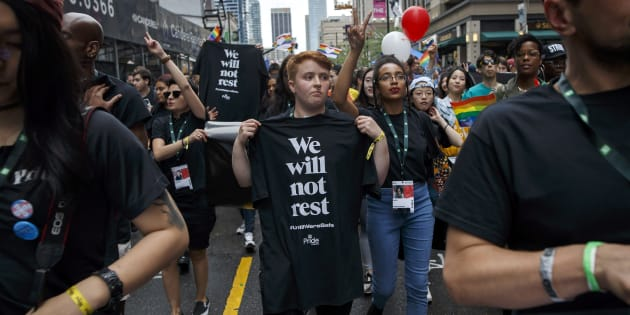 As a tribute to those lost from the community, people march with We Will Not Rest #UntilWe'reSafe posters and t-shirts during the Toronto Pride parade on June 24, 2018.
