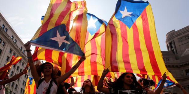 Manifestantes com bandeira separatista da Catalunha.