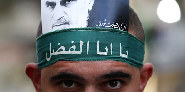 A Hezbollah supporter displays a picture of Iran's late founder of the Islamic Republic Ayatollah Khomeini as he marks Ashura in a southern suburb of the Lebanese capital Beirut on October 1, 2017