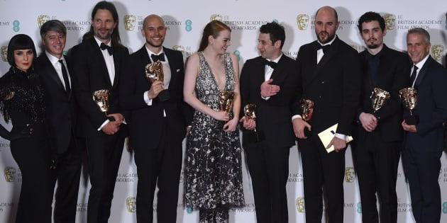 """Les producteurs Fred Berger, Jordan Horowitz et Marc Platt posent avec la récompense du meilleur film pour """"La La Land"""" aux côtés de l'actrice Emma Stone, du réalisateur Damien Chazelle, du cinématographe suédois Linus Sandgre, du compositeur américain Justin Hurwitz et des présentateurs des Bafta ."""