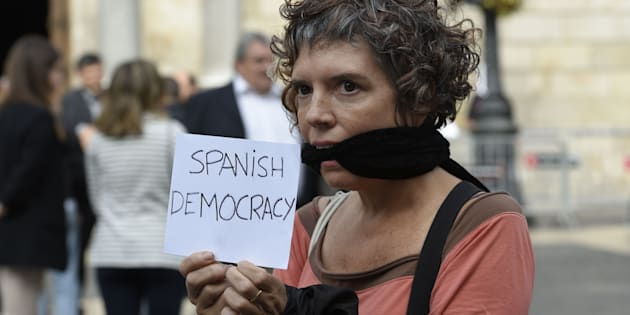 A woman holds a sign reading 'Spanish democracy' during a protest against the arrest of two Catalan separatist leaders in Barcelona on October 17, 2017