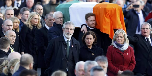 Sinn Feinn President Gerry Adams, centre, walks next to the coffin of Martin McGuinness during his funeral in Londonderry, Northern Ireland, March 23, 2017.