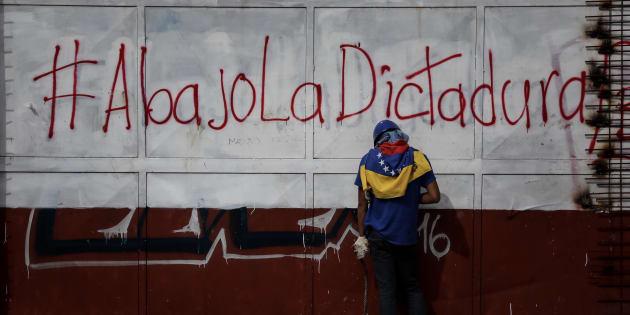 Un manifestante sostiene piedras ante una pintada contra Nicolás Maduro, durante enfrentamientos entre opositores y la Guardia Nacional Bolivariana de ayer jueves en Caracas.