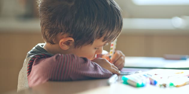 Un niño pequeño dibujando con la mano izquierda.