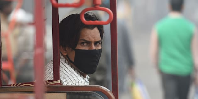 A battery-run tricycle rickshaw operator wearing mask waits for commuters amid heavy smog in the old quarters of New Delhi on November 10, 2017.