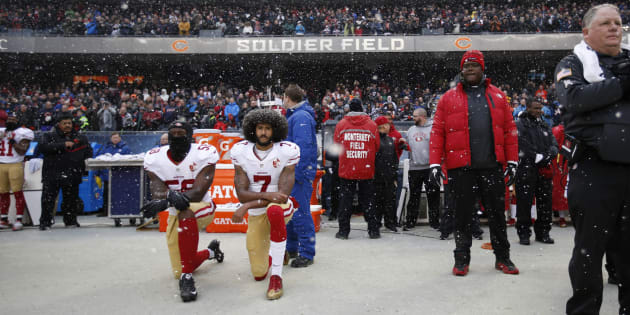 Eli Harold (58) and Colin Kaepernick (7) of the San Francisco 49ers kneel on the sideline, during the anthem, prior to the game against the Chicago Bears at Soldier Field on Dec. 4, 2016 in Chicago, Il.