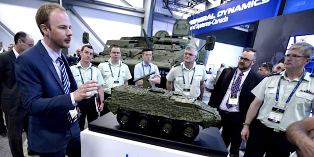 A General Dynamics LAV 6.0 is seen behind people as they gather around a scale model of a the same vehicle at the CANSEC trade show in Ottawa on May 30, 2018.