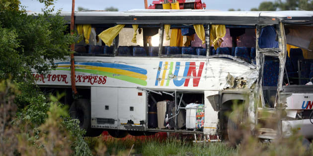 The damage to the side of a tour bus that was involved in a crash on Highway 401 West, near Prescott, Ont., is seen as tow operators work to remove it from a ditch on June 4, 2018.