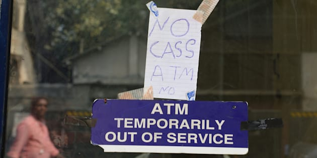 In this photograph taken on November 30, 2016, a handwritten sign stating 'no cash' is hung onto door of an ATM in Mumbai.