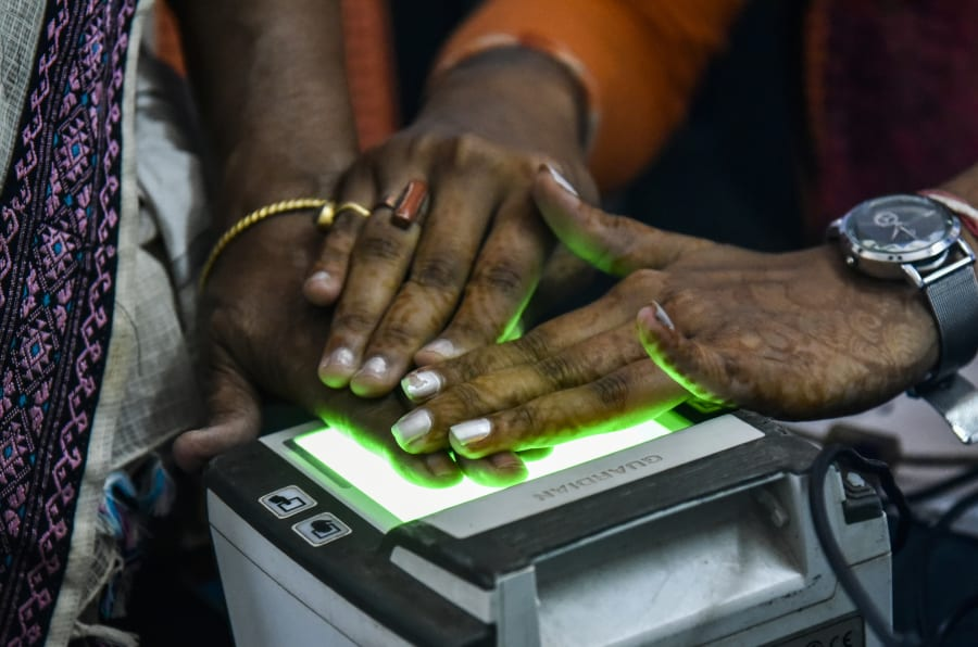 Women scanning fingerprints as an Aadhaar registration process.
