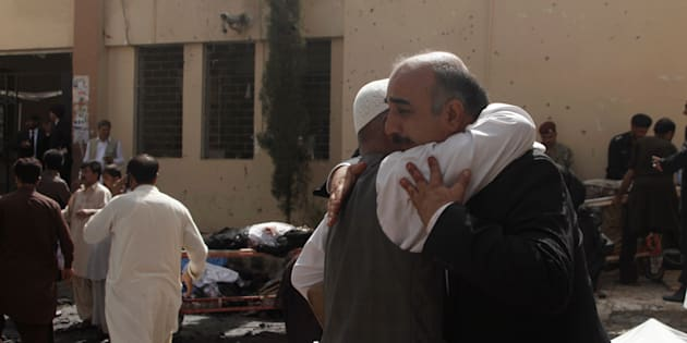 Friends and relatives of victims grieve at the scene of a bomb blast outside a hospital in Quetta.
