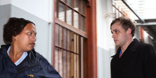 Henri van Breda, right, is led by a South African police woman as he arrives at the Stellenbosch magistrate court in Stellenbosch, South Africa.