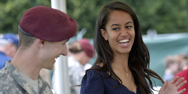 Malia Obama, daughter of US President, (R) smiles as she serves food during a lunch at the United States and Nato military base in Vicenza  on June 19, 2015 .   AFP PHOTO / ANDREAS SOLARO        (Photo credit should read ANDREAS SOLARO/AFP/Getty Images)