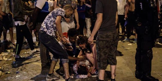 Un hombre yace en el suelo ensangrentado durante los choques entre grupos de jóvenes y la Policía.