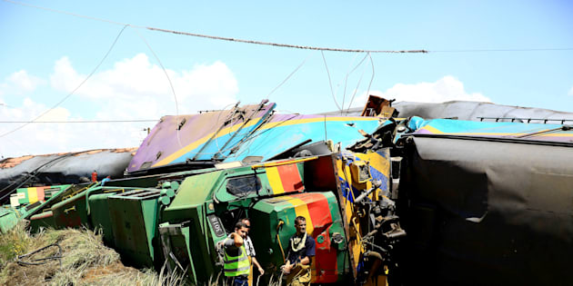 Workers stand next to wreckage after a train crash near Hennenman in the Free State, January 4, 2018.