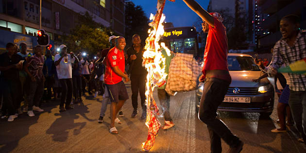 Zimbabweans living in South Africa celebrate by burning a banner with Robert Mugabe?s image after President Robert Mugabe resigns, in Johannesburg, South Africa November 21, 2017.