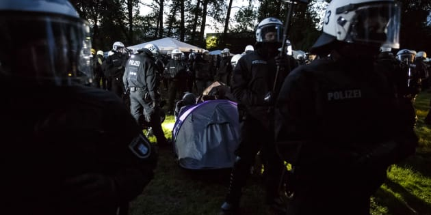HAMBURG, GERMANY - JULY 02: Riot police surround anti-G20 protesters and the sleeping tents the protesters had erected at a protest camp at Entenwerder Park on July 2, 2017 in Hamburg, Germany. While a local court ruled that the protesters are allowed to gather at the park and install tents, police claim the ruling does not allow the protesters to sleep in the tents overnight and later confiscated tents from the protesters. Police are seeking to hinder protesters from disrupting the upcoming G20 economic summit, which takes place July 7-8. (Photo by Morris MacMatzen/Getty Images)