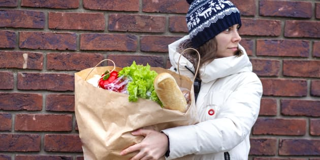 Young woman goes with paper bag of vegetables and food from grocery store on brick wall background. Girl with paper package of food