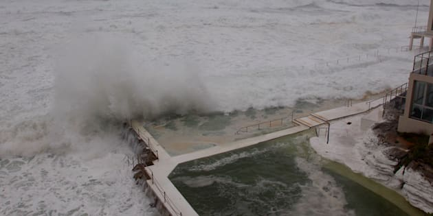 Waves crash into Bondi's Icebergs Pool.