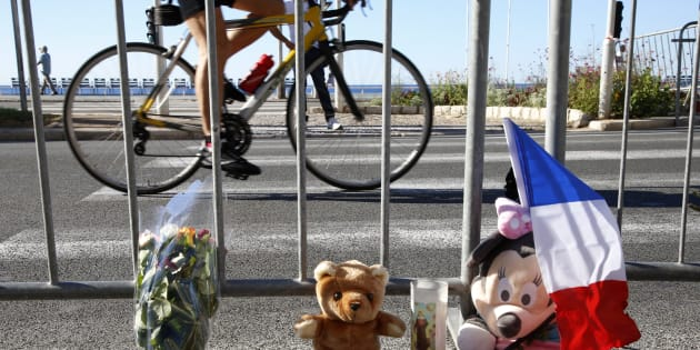 A man cycles past a bouquet of flowers, stuffed toys and a French flag placed in tribute to victims, two days after an attack by the driver of a heavy truck who ran into a crowd on Bastille Day killing scores and injuring as many on the Promenade des Anglais, in Nice, France, July 16, 2016.  REUTERS/Pascal Rossignol
