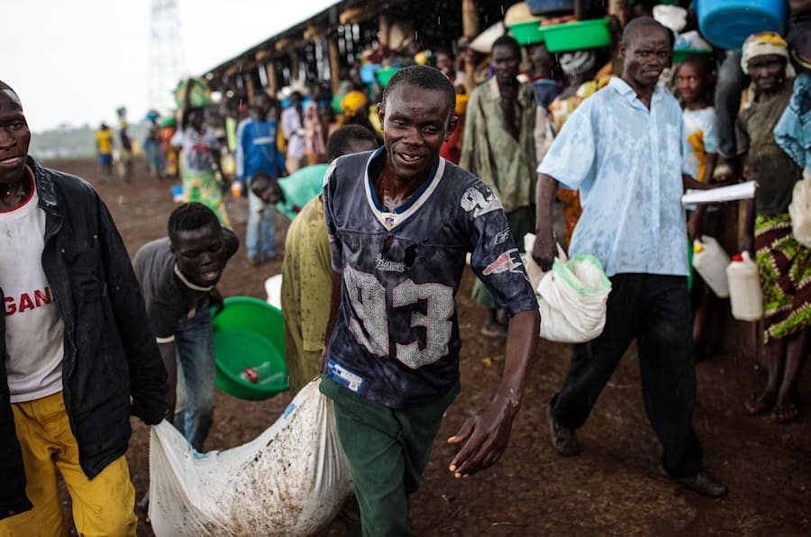 Refugees from the Democratic Republic of Congo carry their food collected from the World Food Programme as it rains in the Kyangwali settlement on April 10, 2018 in Kyangwali, Uganda. According to the UNHCR around 70,000 people have arrived in Uganda from the Democratic Republic of Congo since the beginning of 2018 as they escape violence in the Ituri province.