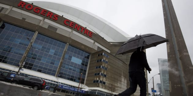 A man walks by the Rogers Centre as reports of falling ice from the CN Tower sparked a closure of parts of the area on Toronto on April 16, 2018.