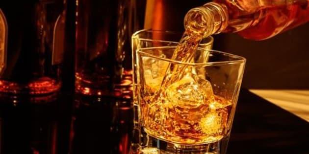 Whisky versé dans un verre avec des glaçons