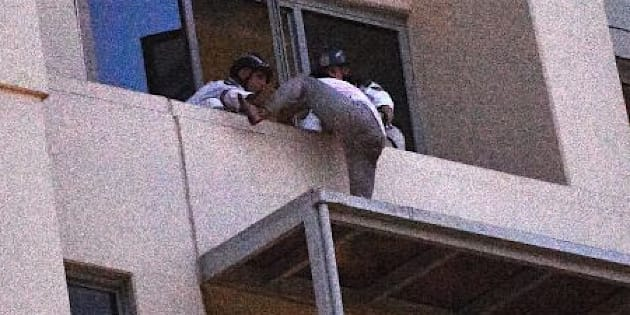 The man remained on the roof of an awning 26 floors high for more than half a day.