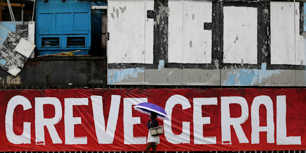 Uma mulher passa em frente ao 'lambe-lambe' que diz 'Greve Geral', no Rio de Janeiro.