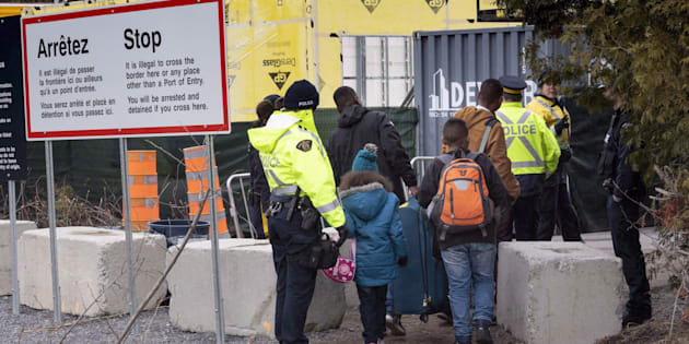 A family claiming to be from Colombia, is arrested by RCMP officers as they cross the border into Canada from the United States as asylum seekers near Champlain, N.Y., on April 18, 2018.