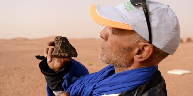 Un chasseur de météorite examine un rocher dans le sud du Maroc, le 25 mars 2018.