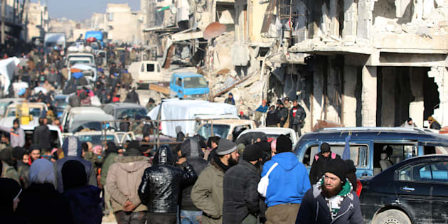 Rebel fighters and civilians wait near damaged buildings to be evacuated from a rebel-held sector of eastern Aleppo, Syria December 18, 2016. Picture taken December 18, 2016. REUTERS/Abdalrhman Ismail