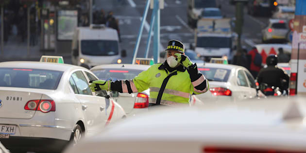 A traffic policeman wears a mask while directing traffic during traffic restrictions intended to curb air pollution in Madrid, Spain, December 29, 2016.  REUTERS/Paul Hanna