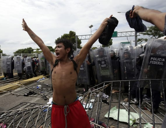 Caravan migrants break border fence, rush Mexico