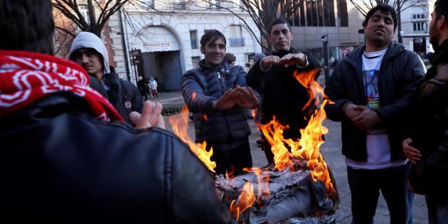 Des hommes se réchauffent autour d'un feu dans le camp de réfugiés installé sur l'avenue Wilson de Saint-Denis, en banlieue parisienne, le 8 décembre 2016.