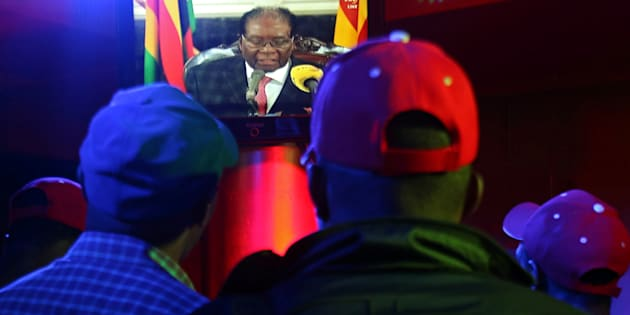 People watch as Zimbabwean President Robert Mugabe addresses the nation on television, at a bar in Harare, Zimbabwe, November 19, 2017.