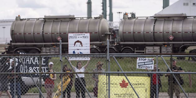 Protestors stand outside the fence as Prime Minister Justin Trudeau visits a Kinder Morgan facility in Edmonton on June 5, 2018.