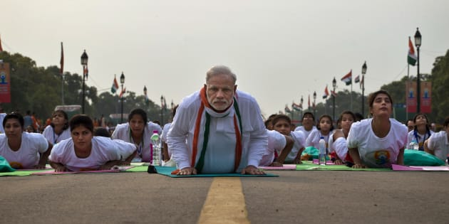 Indian Prime Minister Narednra Modi lies down on a mat as he performs yoga along with thousands of Indians on Rajpath, in New Delhi, India, Sunday, June 21, 2015. Millions of yoga enthusiasts are bending their bodies in complex postures across India as they take part in a mass yoga program to mark the first International Yoga Day.(AP Photo/Saurabh Das)