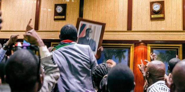 La gente retiró de la pared del Centro de Conferencia Internacional, donde el parlamento tenía su sesión, el retrato del expresidente de Zimbabue, Robert Mugabe, después de su renuncia este 21 de noviembre de 2017 en Harare.