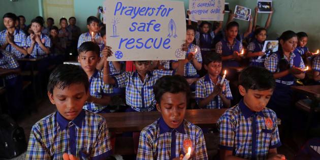 Grupo de alunos reza pelo resgate de meninos em caverna na Tailândia.