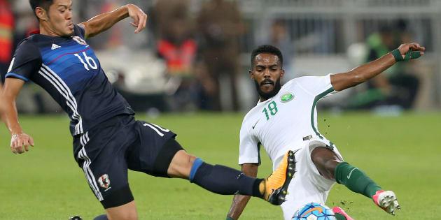 Saudi Arabia's Nawaf Alabid fights for the ball against Japan's Hotaru Yamaguchi.
