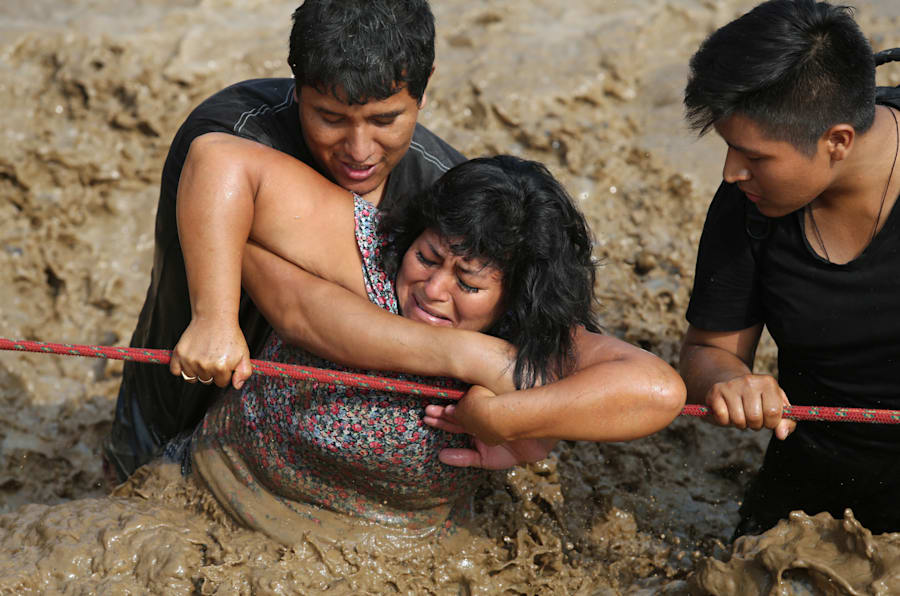 Two men help a woman cross a flooded street after a river overflowed, sending torrents of mud and water rushing through the streets in Huachipa last Friday.