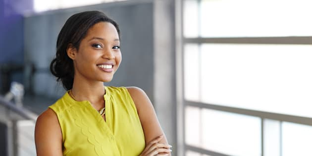 Friendly african american woman standing with arms crossed in a modern bright office