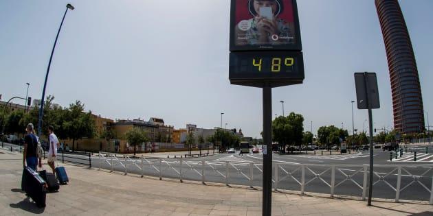 Unos turistas pasan ante un termómetro en Sevilla que marca 48 grados.
