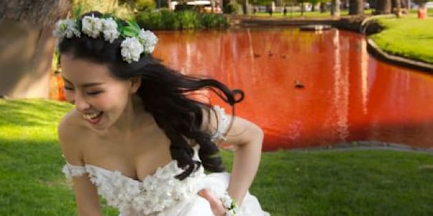 A bride poses alongside the red lake.