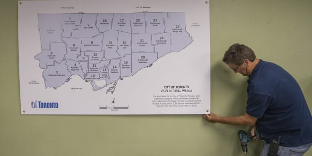 A City employee puts up the map with the 25 council seats on the wall inside the city hall elections office in September.